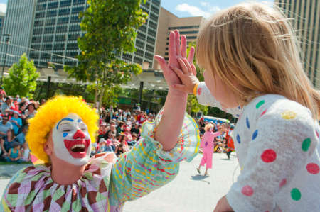 credit union: Adelaide, Australia - November 14, 2015: A young child receiving a high five from a clown in the annual credit union christmas pagaent. The parade is sponsored by South Australian Credit Unions and attracts over 300,000 people annually in the centre of Ad Editorial