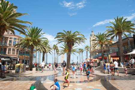 water feature: Adelaide, Australia - January 09, 2016: Children playing in the water feature at Moseley Square, Glenelg. Glenelg is the very popular seaside suburb of Adelaide, South Australia. On warm days tourists and locals flock to the area for shopping, entertainme