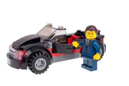 Adelaide, Australia - December 07,2015:A studio shot of a Dealer Lego minifigure with a black sports car from the Lego City 60060 Auto Transporter kit. Lego is extremely popular worldwide with children and collectors. Editorial