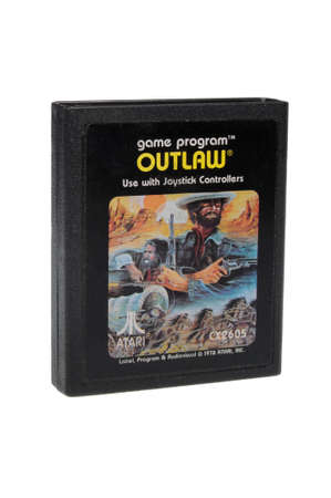 gamers: Adelaide, Australia - February 23 2016: A Studio shot of an Atari 2600 Outlaw Game Cartridge. A popular video game from the 1980s is popular with collectors and retro gamers worldwide. Editorial