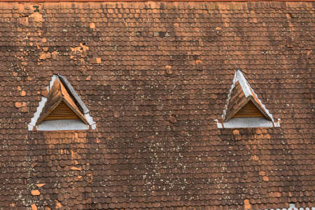 house top: Old house top with traditional roof and two triangle little windows Stock Photo