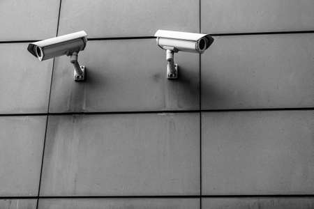 surveillance camera: Two surveillance cameras black and white on the wall opposite each other
