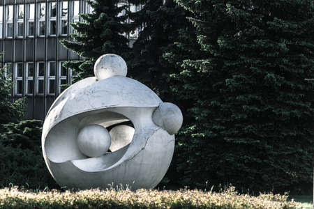 fur tree: Ball white modern art sculpture with fur tree and building background
