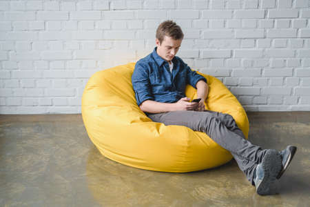 #66421548   Attentive Young Man Sitting In Yellow Bean Bag Chair And Using  Black Smartphone Indoors
