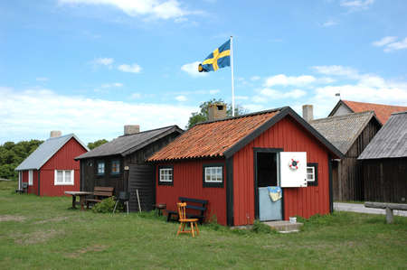 Row of small houses with the Swedish flag in the center photo