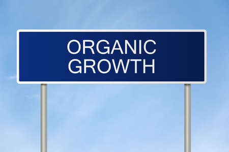 A blue road sign with white text saying organic growth photo
