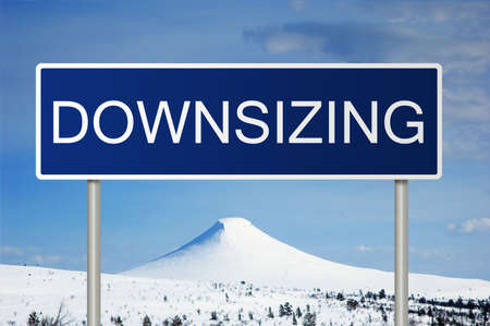 downsizing: A blue road sign with white text saying Downsizing