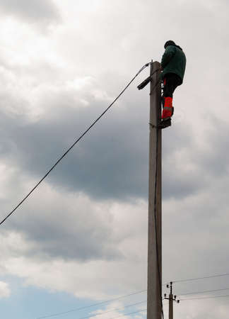 climbed: electrician climbed to the top of a concrete pillar and fixes it on cable