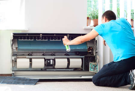 aire acondicionado: hombre limpia el aire acondicionado