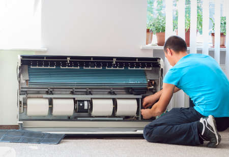 condition: man cleans the air conditioning Stock Photo