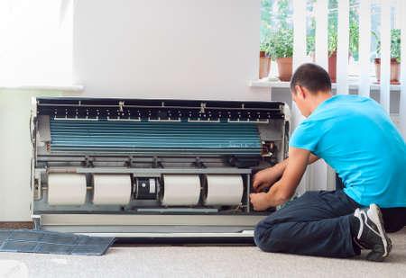 Uomo pulisce l'aria condizionata Archivio Fotografico - 41884900