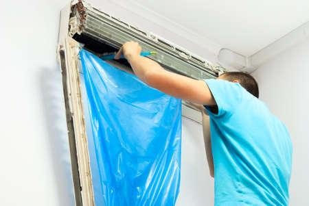 L'uomo pulisce l'aria condizionata Archivio Fotografico - 41884914