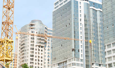 fasade: boom crane on the background of new buildings Stock Photo
