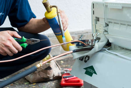 master performs soldering copper pipe gas burner Stockfoto