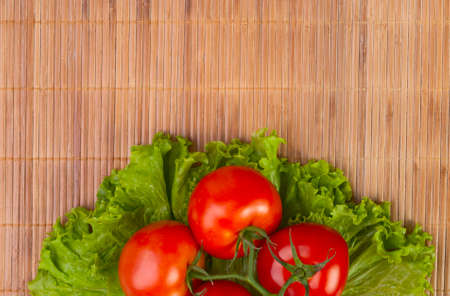 branch of tomato and lettuce lying on a bamboo table cloth