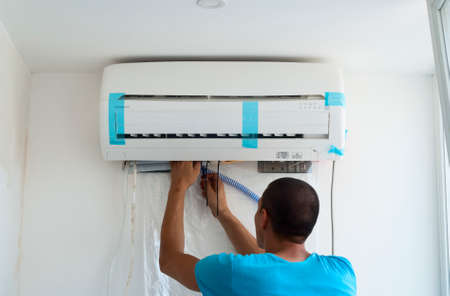 man in air: man installs indoor unit of the air conditioner
