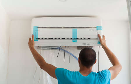 room air: man installs indoor unit of the air conditioner