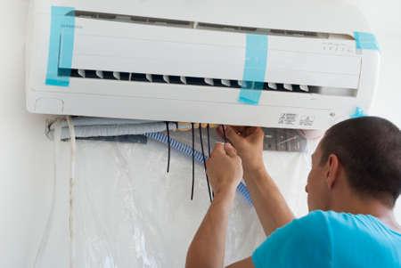 aire acondicionado: El hombre instala la unidad interior del acondicionador de aire
