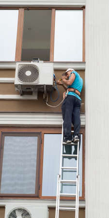 man standing on a ladder and sets the air conditioner outdoor unit 免版税图像