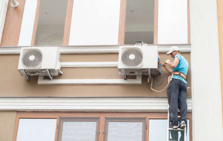 man staande op een ladder en zet de airco buitenunit Stockfoto