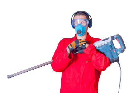 hands in the air: a man in overalls holding a hammer with a huge drill Stock Photo