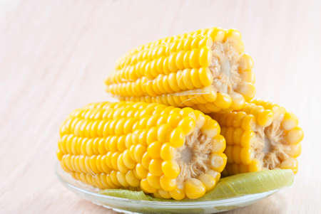 Three cobs of sweet corn cooked in a dish on a wooden table