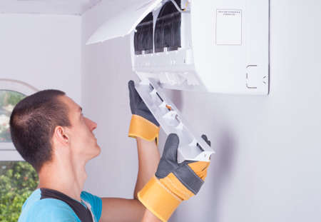 Uomo imposta lo sportellino per l'unità interna del climatizzatore Archivio Fotografico - 42118333