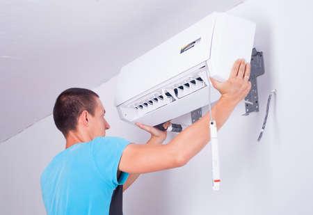 man installs indoor unit of the air conditioner