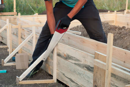 protruding: Worker saws hacksaws protruding part wooden formwork Stock Photo