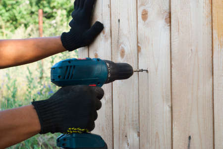 installer: installer collects wooden structure using a cordless screwdriver Stock Photo