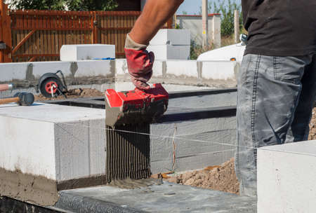 aligning: builder deals in the adhesive solution aerated concrete block