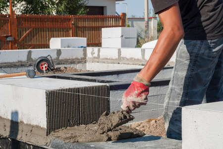 aligning: Builder does cement sand mortar on the surface of the basement