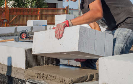 builder puts on grout aerated concrete block Stockfoto