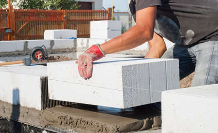 aligning: builder puts on grout aerated concrete block Stock Photo