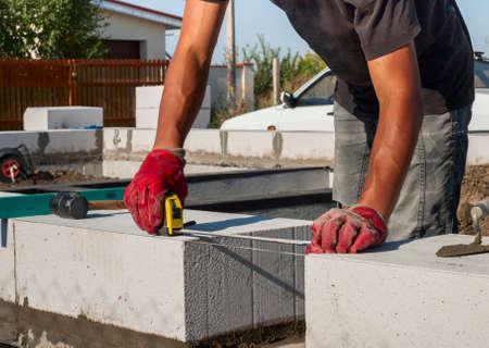 aligning: Builder measures the distance between the blocks