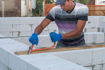 aerated: Builder makes a groove in aerated concrete Stock Photo
