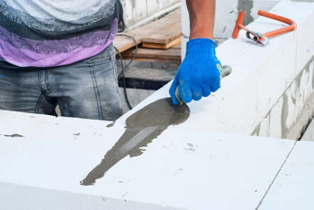 aligning: builder reinforces laying of aerated concrete blocks