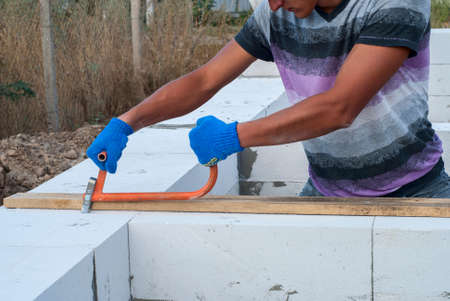 deepening: Builder makes a groove in aerated concrete Stock Photo