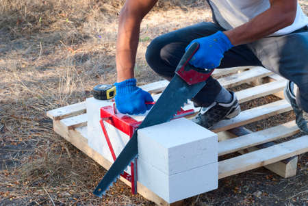 prefabricated buildings: builder cut into pieces aerated concrete block Stock Photo