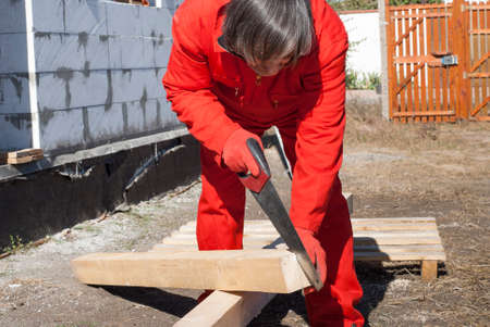 wooden beams: carpenter cuts off a piece of wooden beams Stock Photo