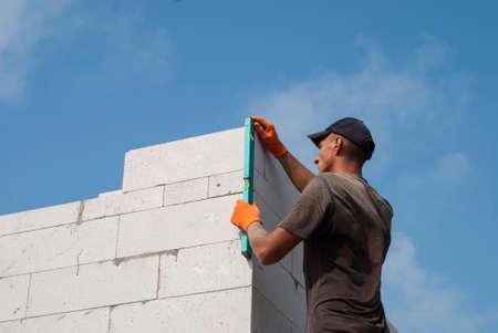 albañil: Constructor verifica la veracidad de los muros de mampostería de hormigón celular Foto de archivo