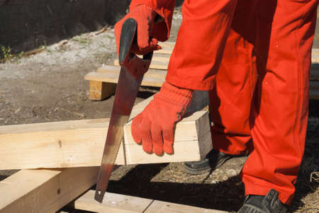 off cuts: carpenter cuts off a piece of wooden beams Stock Photo