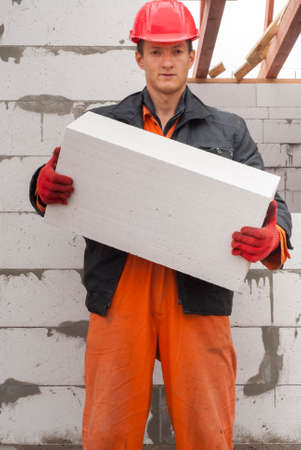 aligning: master mason holding a large block of aerated concrete
