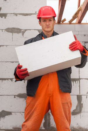 hollow walls: master mason holding a large block of aerated concrete