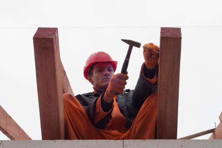 roof framing: builder hammers a nail into a wooden beam