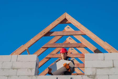 aerated: master mason holding a large block of aerated concrete