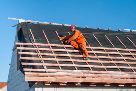 Worker installs bearing laths on the truss system