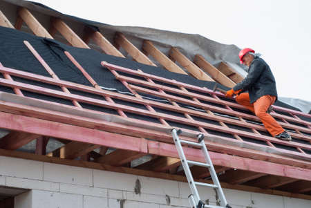 roofing membrane: Worker installs bearing laths on the truss system