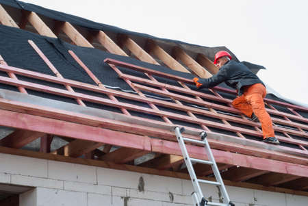 laths: Worker installs bearing laths on the truss system