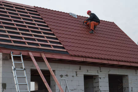 Builder assembles roof tiles of metal